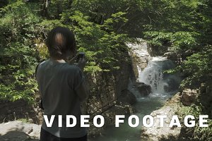 Young girl takes photo of small waterfall, Georgia