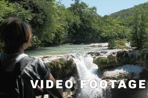 Young girl looks to the small waterfall, Georgia, Martvili
