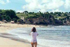 Beautiful young woman in bikini posing on the beach of a tropical island of Bali, Indonesia.