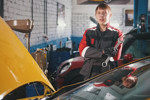Portrait of a young car mechanic in overalls in a car workshop