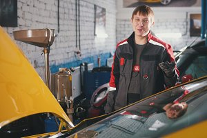Young car mechanic in overalls in a car workshop