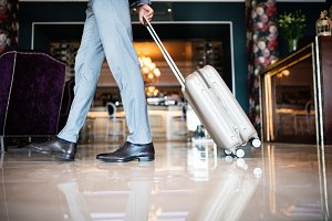 Businessman entering hotel with luggage.