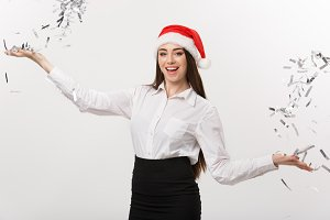 Christmas celebration concept - Young business woman throwing confetti for celebrating Christmas day isolated on white background.