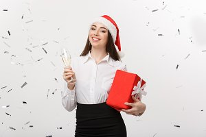 Christmas Concept - young business woman holding champagne and present with confetti background.