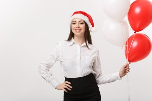 Business Concept - Beautiful young confident business woman with santa hat holding balloon celebrate for Christmas.