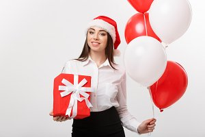 Christmas Concept - young happy caucasian business woman with santa hat holding gift box and balloon with copy space on side.