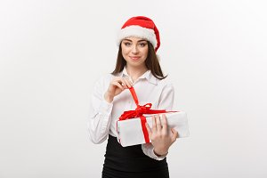 Christmas Concept - young happy caucasian business woman with santa hat smiling while open gift box with copy space on side.
