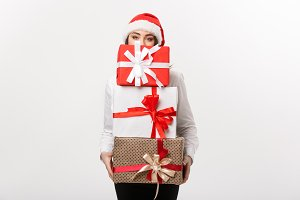 Business Concept - Beautiful young caucasian business woman with santa hat hiding behide a lot of christmas gift boxes with copy space on side.