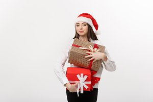 Business Concept - Beautiful young caucasian business woman with santa hat holding a lot of christmas gift boxes with copy space on side.