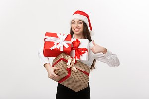 Business Concept - Beautiful young caucasian business woman with santa hat holding a lot of gift boxes and showing thump up.