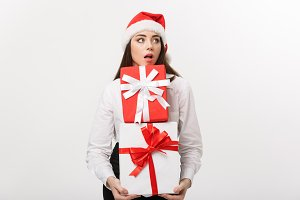 Business Concept - Beautiful young caucasian business woman with santa hat holding a lot of gift boxes with surprising facial expression.