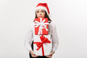 Business Concept - Beautiful young caucasian business woman with santa hat holding a lot of gift boxes with worry facial expression.