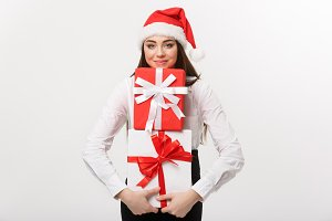 Business Concept - Beautiful young caucasian business woman with santa hat holding a lot of gift boxes with copy space on side.