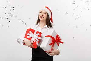 Business Concept - Beautiful young caucasian business woman with santa hat holding gift box with confetti celebration background.