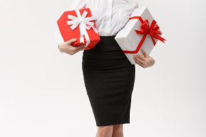 Business Concept - Beautiful young caucasian business woman with santa hat holding gift boxes with copy space on side.