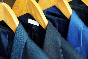 Row of men's suits hanging on rack