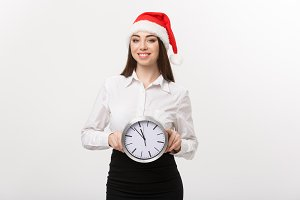 Time management concept - Young happy business woman with santa hat holdinga clock isolated over white background.