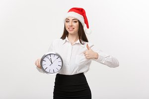 Time management concept - Young business woman with santa hat holding a clock and showing thump up isolated over white background.