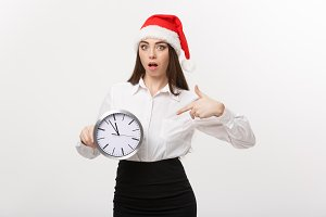 Time management concept - Young business woman with santa hat holding and pointing a clock isolated over white background.