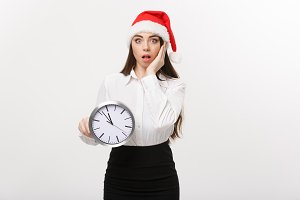 Time management concept - Young business woman with santa hat holding a clock isolated over white background.