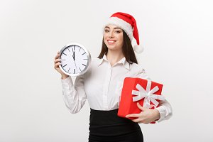 Time management concept - Young business woman with santa hat holding a clock and present isolated over white background.