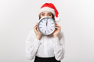 Time management concept - Young business woman with santa hat hiding behind a clock isolated over white background.
