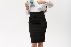 Christmas and finance concept - Young business woman showing money and thumb up in front of camera.