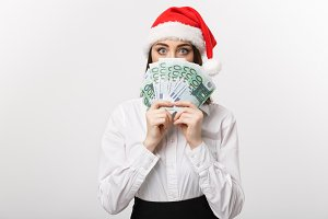 Christmas and finance concept - Young business woman showing money closing her face with surprise expression.