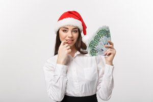 Christmas and Financial concept - Young confident business woman showing money in front of her with happy face.