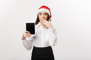 Business Concept - young caucasian business woman in Christmas theme showing digital tablet with surprising facial expression.