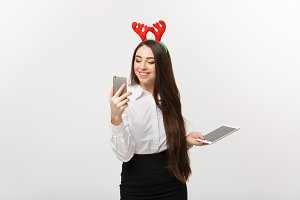 Business Concept - young caucasian business woman in Christmas theme playing moblie phone with surprising facial expression.