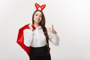 Christmas Concept - Young beautiful business woman in christmas theme holding santa red bag giving thumb up.