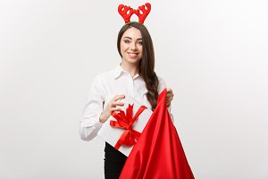 Christmas Concept - Young beautiful business woman happy with present in santa bag.