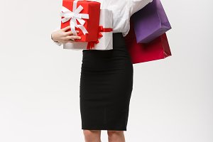 Christmas Concept - beautiful business woman holding shopping bags and present with copy space.