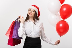 Christmas Concept - beautiful caucasian business woman happy holding shopping bags and ballons.