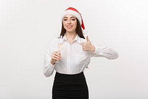 Christmas Celebration - Young beautiful business woman celebrating christmas with glass of champagne and showing thumb up.
