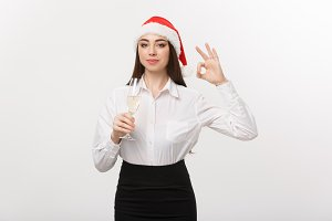 Christmas Celebration - Young beautiful business woman celebrating christmas with glass of champagne and showing ok sign.