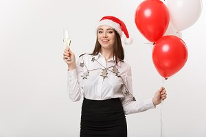 Christmas Celebration - Young beautiful business woman celebrating christmas with glass of champagne and confetti background.