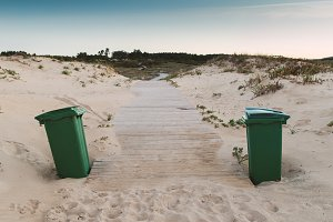 Two green trash can on the beach