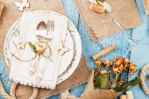 Tableware and silverware with dry flowers and different decorations
