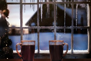 Two mugs with coffee on a background of a winter window. Snow falling, icicles
