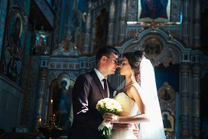 young couple groom and bride on church background