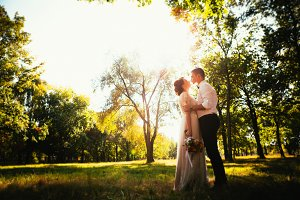 The bride and groom in the background of park trees