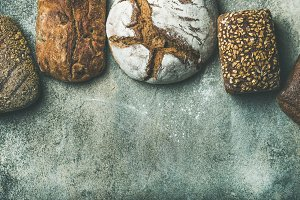 Top view of bread loaves over grey background, copy space