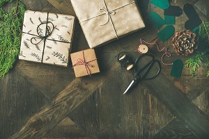Flat-lay of gift boxes, rope, fur branches, scissors, wooden background