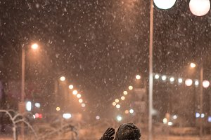 Girl enjoying snowfall night