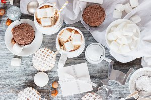 Cups with cacao and marshmallow, cupcakes and different Christmas decorations