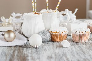 Cups with cacao and marshmallow, cupcakes and different Christmas decorations, wooden background