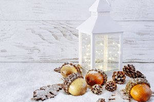 Christmas Lantern on snow and acorns