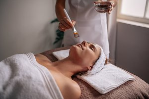 Woman getting facial mask at spa sal
